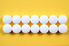 Píldoras farmacéuticas redondas blancas en fondo amarillo fotografía de archivo