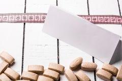 Píldoras, hoja de papel en blanco y cinta métrica rosada sobre el fondo de madera blanco Fotografía de archivo libre de regalías