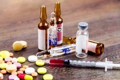 Píldoras, inyector y ampollas en fondo de madera Foto de archivo