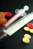 Píldoras, jeringuilla y termómetro Fotos de archivo
