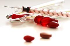 Píldoras, jeringuilla y termómetro. Imagen de archivo