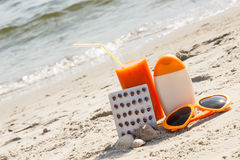 Píldoras, jugo de zanahoria y accesorios médicos para tomar el sol en la playa, la vitamina A y el moreno hermoso, duradero Fotos de archivo
