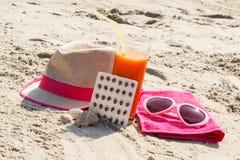 Píldoras, jugo de zanahoria y accesorios médicos para tomar el sol en la playa, la vitamina A y el moreno hermoso, duradero Fotografía de archivo libre de regalías