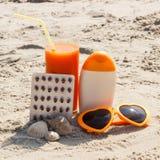 Píldoras, jugo de zanahoria y accesorios médicos para tomar el sol en la playa, la vitamina A y el moreno hermoso, duradero Foto de archivo