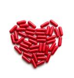 Píldoras largas rojas en una forma del corazón Imágenes de archivo libres de regalías