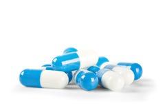 Píldoras médicas azules y blancas con las sombras Imágenes de archivo libres de regalías