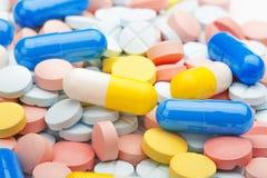 Píldoras médicas azules y blancas en un fondo de píldoras coloreadas Foto de archivo