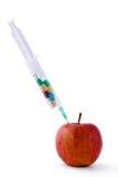 Píldoras médicas del witn de la jeringuilla y manzana roja que mienten el escritorio, aislado en el fondo blanco Fotos de archivo libres de regalías