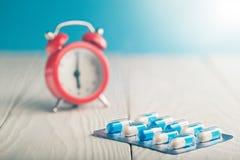 Píldoras médicas en la tabla y el reloj de madera en el fondo Tiempos médicos del consumo de drogas, el horario del tratamiento m imagen de archivo libre de regalías