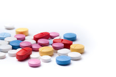 Píldoras médicas multicoloras en el fondo blanco Imágenes de archivo libres de regalías