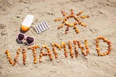 Píldoras médicas, vitamina D de la inscripción y accesorios para tomar el sol en la arena en la playa, tiempo de verano y forma d Foto de archivo