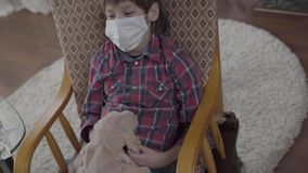 Píldoras, medicina, jarabe en la tabla y niño en mascarilla en la mecedora con el juguete beige del perro almacen de metraje de vídeo