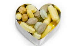 Píldoras multi de la vitamina en el corazón aislado Fotos de archivo libres de regalías