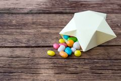 Píldoras multicoloras dulces del caramelo en la caja de regalo de papel en la forma de imagen de archivo libre de regalías