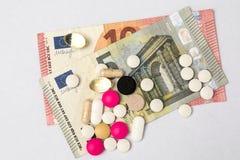 Píldoras multicoloras y billetes de banco duros del cápsula y euro Foto de archivo