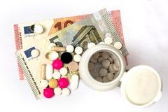 Píldoras multicoloras y billetes de banco duros del cápsula y euro Fotos de archivo