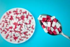 Píldoras o cápsulas blancas rojas en una placa y en una cuchara imagen de archivo