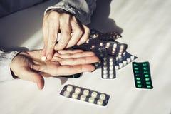 Píldoras o cápsulas de la medicina con las viejas manos de los woman's en el fondo blanco con el espacio de la copia Paquete de fotografía de archivo libre de regalías