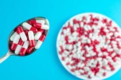Píldoras o cápsulas farmacéuticas de la medicina en una placa y en una cuchara imagen de archivo libre de regalías