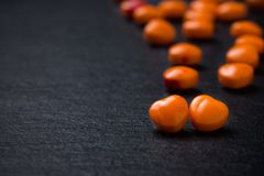 Píldoras o caramelo en forma de corazón anaranjadas en negro del grunge Imagen de archivo libre de regalías