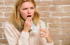 Píldoras para romper fiebre Remedios del dolor de cabeza y de la fiebre La mujer despeinó el agua de cristal del control de la bu fotografía de archivo