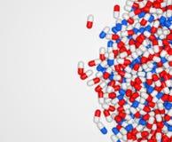 Píldoras que caen en el fondo blanco Fotos de archivo