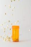 Píldoras que caen en y alrededor de la botella de la medicina Imagen de archivo libre de regalías