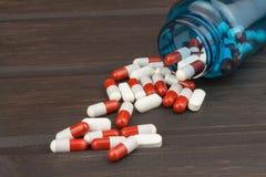 Píldoras que desbordan una botella abierta Doping en deporte Abuso de los esteroides anabólicos para los deportes fotos de archivo