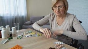 Píldoras que lanzan de la mujer mayor triste de la tabla y del griterío, problema de salud, depresión metrajes