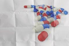 Píldoras que se derraman fuera de la botella de píldora en el papel arrugado Imagenes de archivo