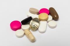 Píldoras redondas y cápsulas duras y suaves ovales en el fondo blanco Imágenes de archivo libres de regalías