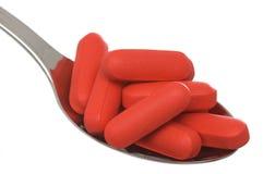 Píldoras rojas de mayo en pequeña cuchara Imágenes de archivo libres de regalías