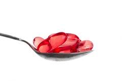 Píldoras rojas en la cuchara Foto de archivo libre de regalías