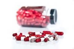 Píldoras rojas y blancas en blanco Imagenes de archivo