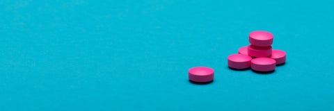 Píldoras rosadas brillantes en fondo coloreado azul marino Medicación y bandera del web de las píldoras de la prescripción Foto de archivo