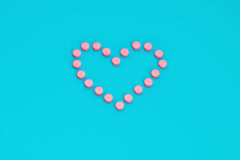 Píldoras rosadas en dimensión de una variable del corazón Fotos de archivo libres de regalías