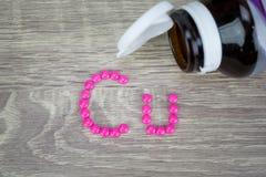 Píldoras rosadas que forman forma al alfabeto del Cu en el fondo de madera Fotos de archivo libres de regalías