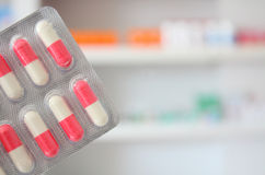 Píldoras rosadas y blancas de las medicinas de las cápsulas de los antibióticos Foto de archivo libre de regalías