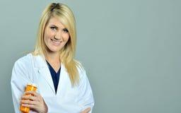 Píldoras rubias bastante jovenes del profesional del cuidado médico Imagen de archivo libre de regalías