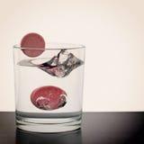 Píldoras solubles que caen en el vidrio de agua Imagen de archivo libre de regalías