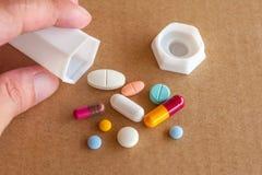 Píldoras, tabletas coloridas y cápsulas derramadas a mano Fotografía de archivo libre de regalías