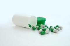 Píldoras verdes una botella en el fondo blanco Imagenes de archivo