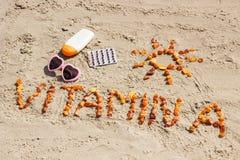 Píldoras, vitamina A de la inscripción y accesorios médicos para tomar el sol en la arena en el moreno de la playa, sano, hermoso Fotografía de archivo libre de regalías