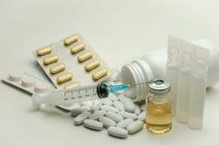 Píldoras, vitaminas y jeringuilla para la inyección con las medicaciones aisladas en el fondo blanco Foto de archivo libre de regalías
