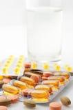Píldoras y agua Fotos de archivo libres de regalías