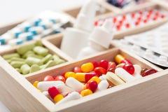 Píldoras y ampollas médicas en caja de madera Fotos de archivo libres de regalías