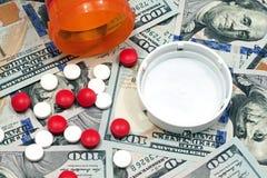 Píldoras y botella de píldora en cientos billetes de dólar Foto de archivo