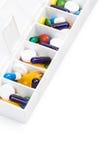 Píldoras y cápsulas del color en organizador de la píldora Fotografía de archivo libre de regalías