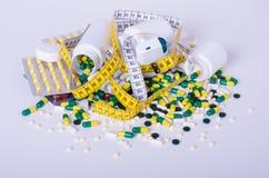 Píldoras y cinta métrica aisladas, dieta del concepto imagenes de archivo