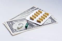 Píldoras y dólares Fotografía de archivo libre de regalías